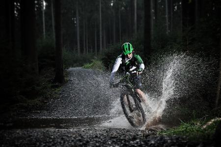 cyclists: Mountain biker speeding through forest stream. Water splash in freeze motion.