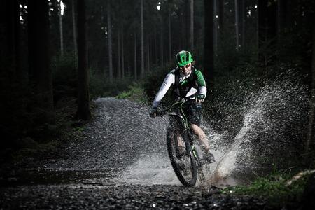 Mountainbiker versnellen door bos stroom. Water splash in bevriezen beweging. Stockfoto