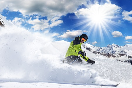 in action: Skier in high mountains during sunny day. Stock Photo