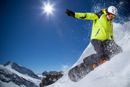 freeride: Snowboarder in high mountains during sunny day.