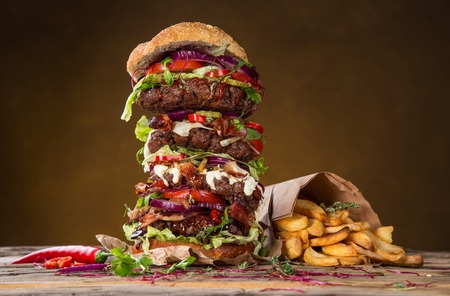 Delicious big hamburger on wooden background photo