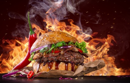 Delicious burger with fire flames Stock Photo
