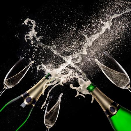 champagne flutes: Champagne explosion on black background, celebration theme.