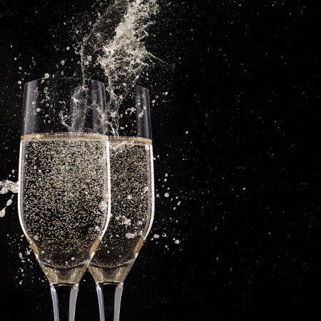 sparkling wine: Champagne flutes on black background, celebration theme.