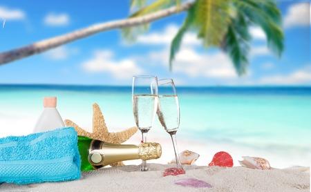 beach happy new year: Champagne flutes on sunny beach, celebration theme. Stock Photo
