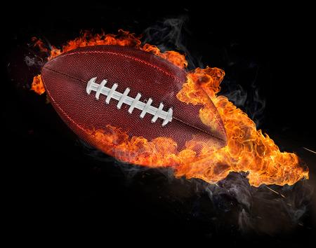 lanzamiento de bala: pelota de rugby volando con llamas de fuego aislado en negro. Foto de archivo