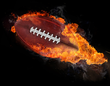 flying rugby ball with fire flames isolated on black. photo
