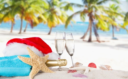 anniversary beach: Champagne flutes with santa cap on sunny beach, celebration theme.