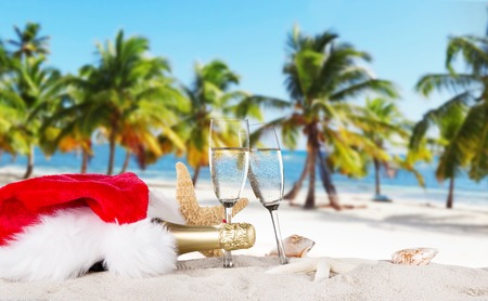 beach happy new year: Champagne flutes with santa cap on sunny beach, celebration theme.