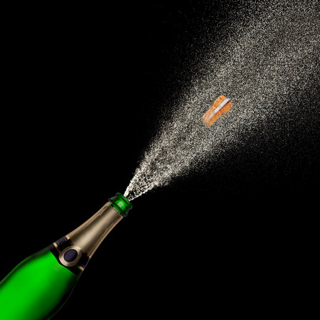 Champagne explosion on black background, celebration theme.