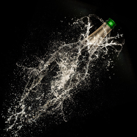 Abstract champagne bottle on black background, celebration theme. photo