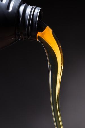 Motorolie gieten over zwarte achtergrond