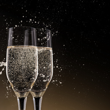 champagne glasses: Champagne flutes on black background, celebration theme.