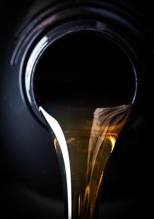 Olio motore versando su sfondo nero