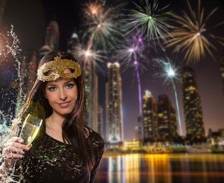 congratulating: Young brunette woman with champagne glass in city at night. Celebration theme. Stock Photo