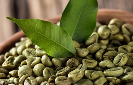 green coffee beans in wooden bowl, close-up. Imagens