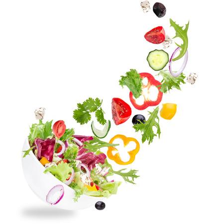 ensalada de tomate: Ensalada fresca con los vehículos voladores ingredientes aislados en un fondo blanco.