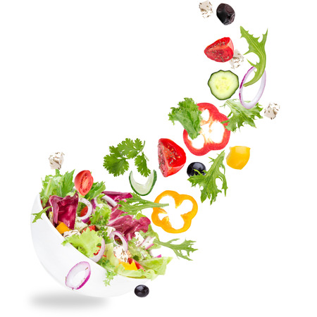 salads: Fresh salad with flying vegetables ingredients isolated on a white background.