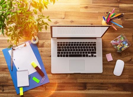 Werkplek met notebook, kantoorbenodigdheden en houten bureau.