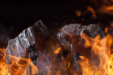 carbon emission: Coal lumps with fire flames, close-up Stock Photo