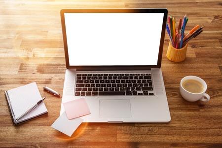 oficina desordenada: Lugar de trabajo con ordenador portátil, material de oficina y escritorio de madera.