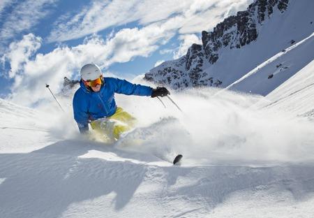 Skier ski afdaling in het hooggebergte tijdens zonnige dag.