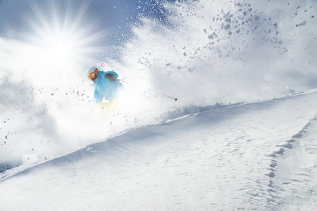 downhill: Skier skiing downhill in high mountains during sunny day.