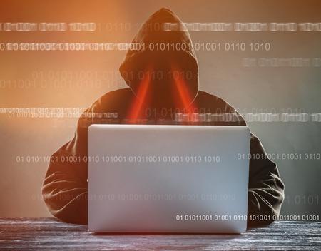 ノート パソコンとフード付きのハッカー。オンライン ネットワークの危険性。
