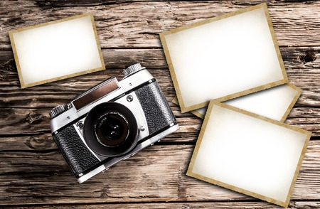 Old vintage camera on a wooden background with blank photo frames.