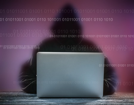 anonym: A hacker with a hood with laptop. Online network danger.