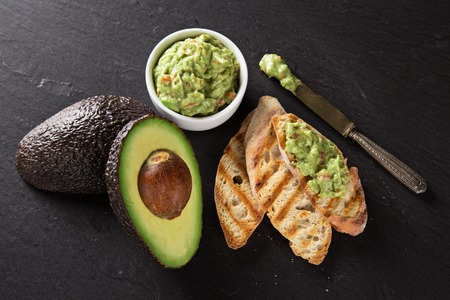 Guacamole with bread and avocado on stone background Фото со стока