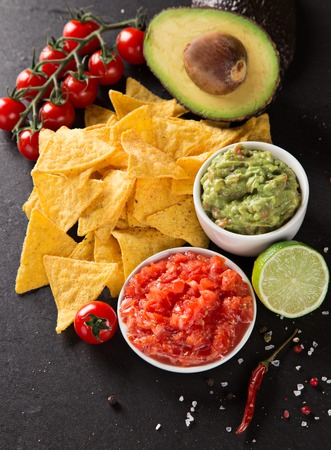 chilli sauce: Green Guacamole with nachos and avocado on stone background