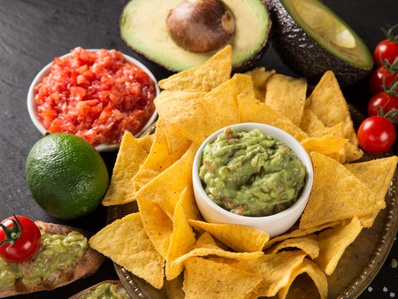 chips and salsa: Green Guacamole with nachos and avocado on stone background