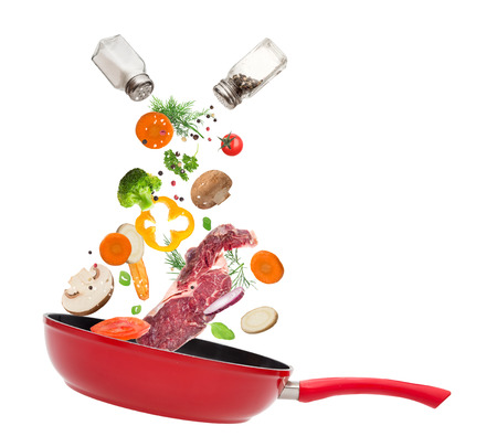 ingredient: Pan with vegetables in freeze motion isolated on white .