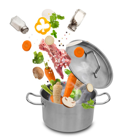 Fresh vegetables falling into stainless steel pot isolated on white background. Stock fotó