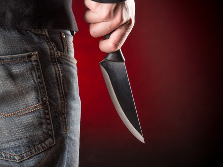 young knife: Criminal with knife in hand Stock Photo