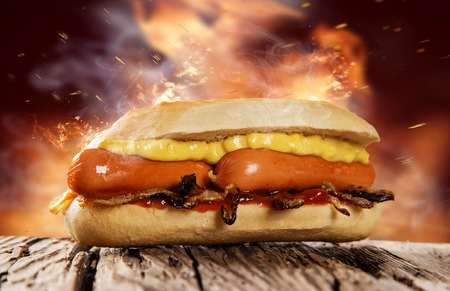 Hot dog with mustard and ketchupon wooden table. Standard-Bild
