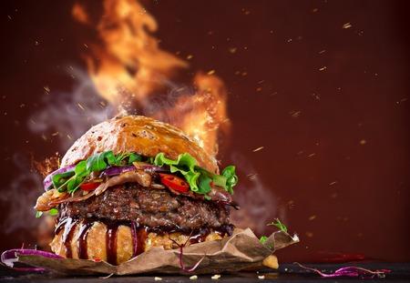 hamburguesa: Deliciosa hamburguesa con llamas de fuego sobre fondo de madera