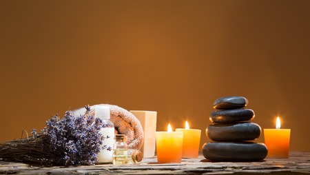 relaxation background: Spa still-life with stacked of stone and burning candles, close-up. Stock Photo