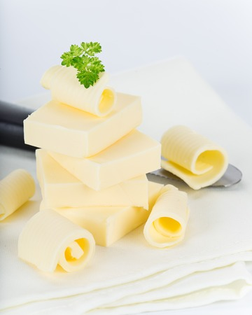 butterfat: Curls of fresh butter on white background