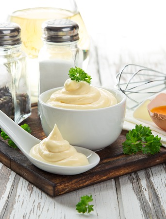 mayonnaise: Mayonnaise in bowl on wooden table.