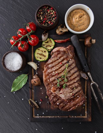 Beef rump steak on black stone table, close-up. Stock Photo - 38612508