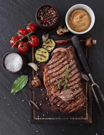 carne asada: Filete de lomo de carne de vaca en la mesa de piedra negro, primer plano.