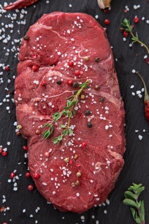 rump steak: Raw beef rump steak on black table, close-up