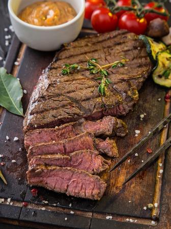 rump steak: Beef rump steak on black stone table, close-up.