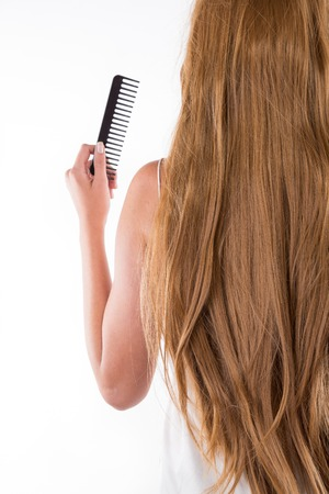horizontal haircut: cutting young beautiful brunette womans hair with scissors
