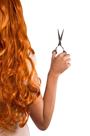 cutting young beautiful red-haired womans hair with scissors Stock Photo