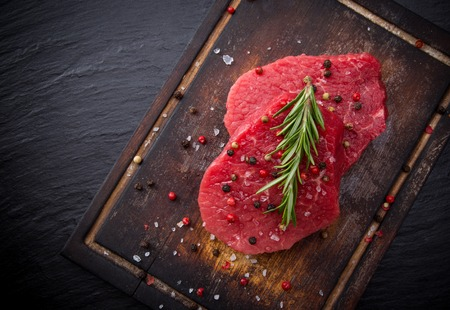 mignon: Raw beef steak on wooden table, close-up