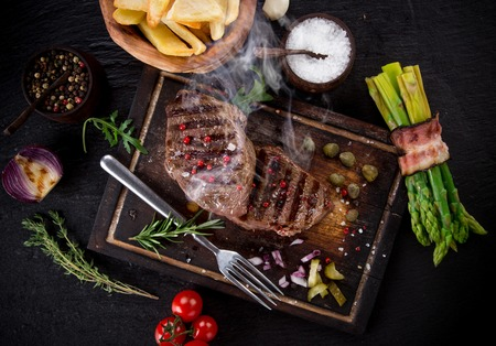 black stone: Beef steak on black stone table, close-up Stock Photo