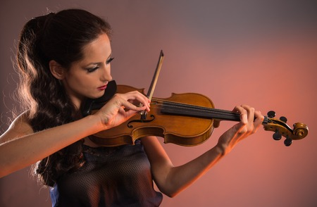 woman violin: Young woman with violin on dark background